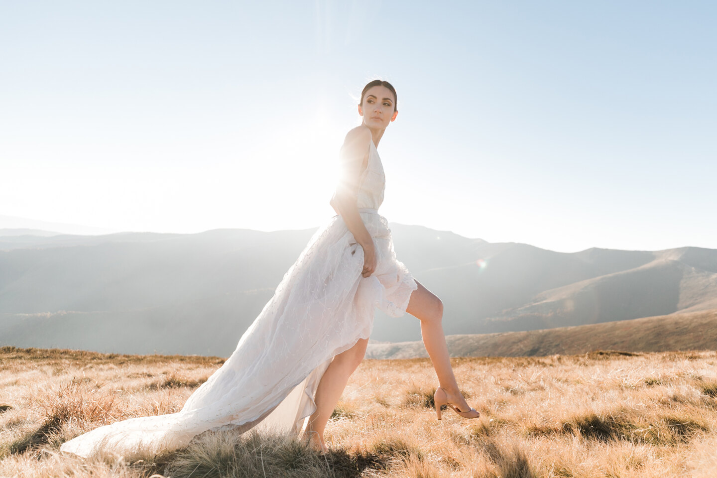 Wedding Photographer in Italy: The bride in a wedding dress on a background of mountains lit by the sun.