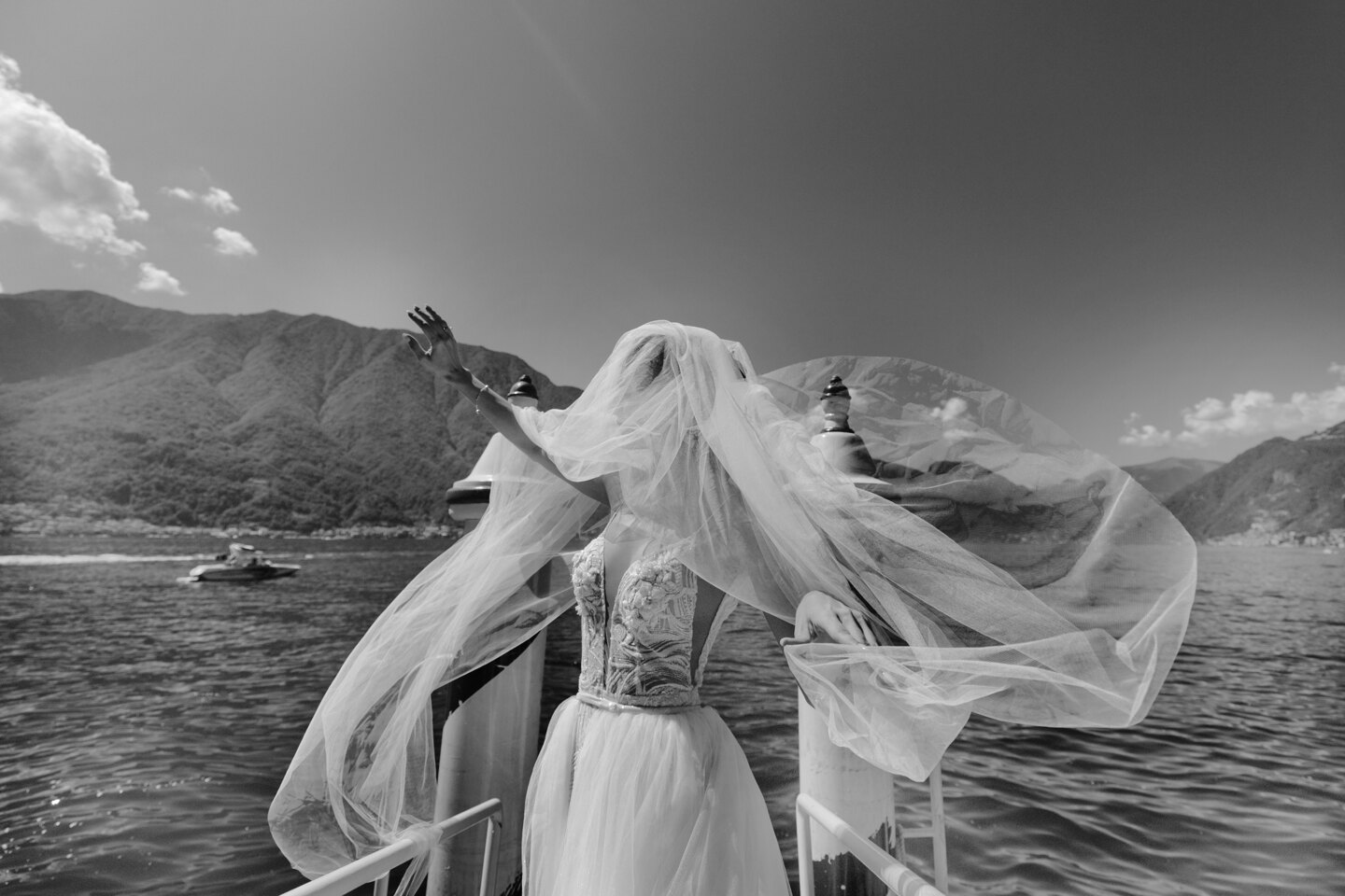 Wedding Photographer in Italy: The bride in a white wedding dress is trying to curb her wedding veil, which is greatly destroyed by the wind, on the lake, among the mountains