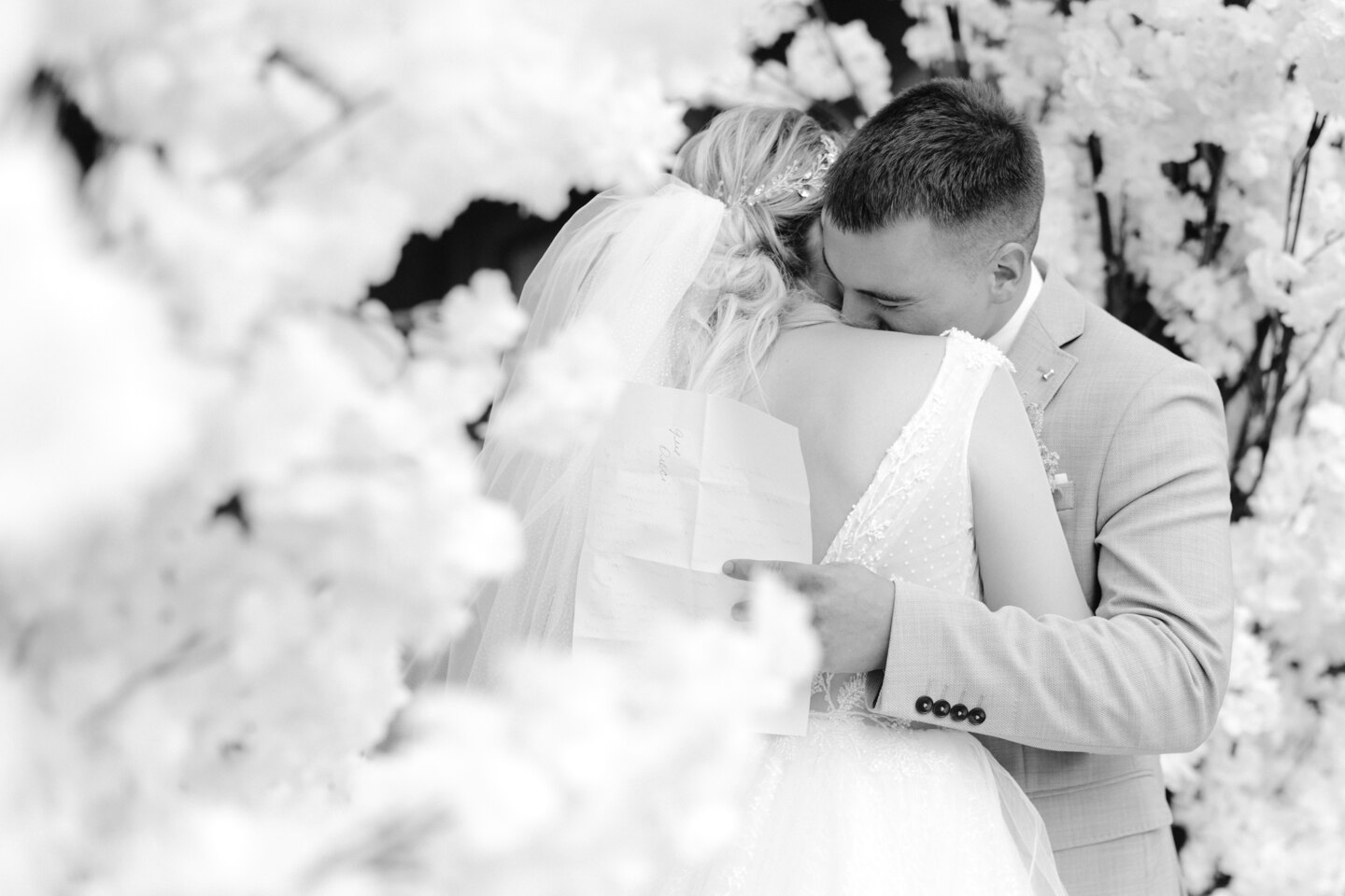 Wedding Photographer in Italy: The groom sincerely hugs his bride, after the words of the vow, which are written on a sheet in his hands