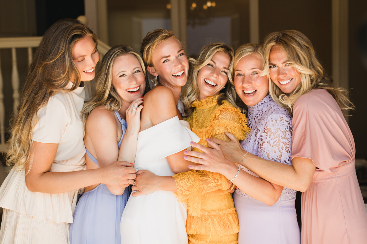 Wedding Photographer in Italy: Cheerful and smiling girlfriends of the bride posing with her on a morning photo shoot in a hotel room