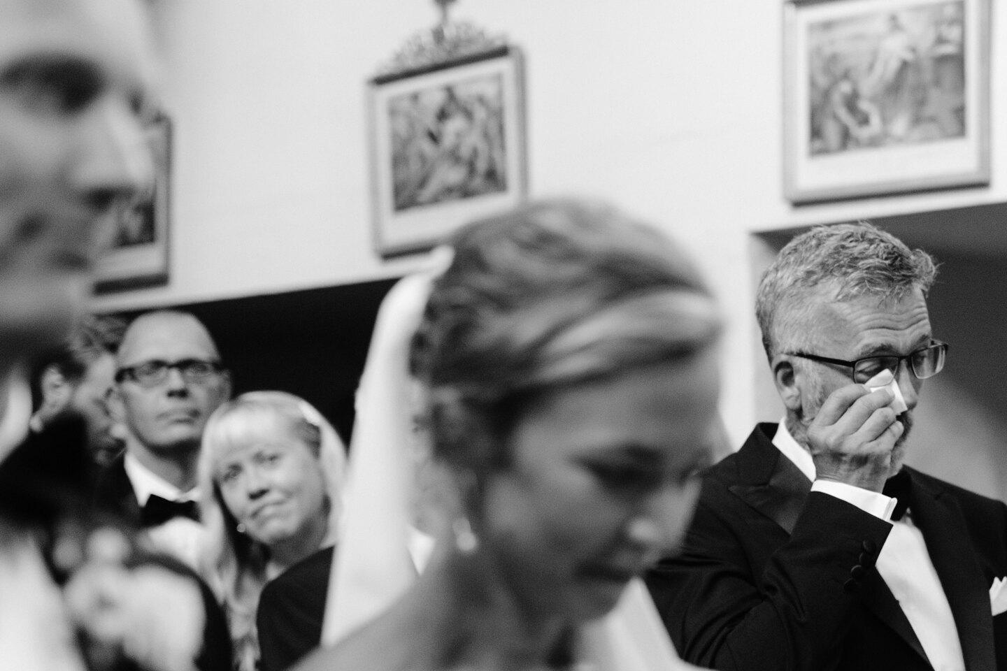 Wedding Photographer in Rome: A man in a church wipes his tears with a handkerchief