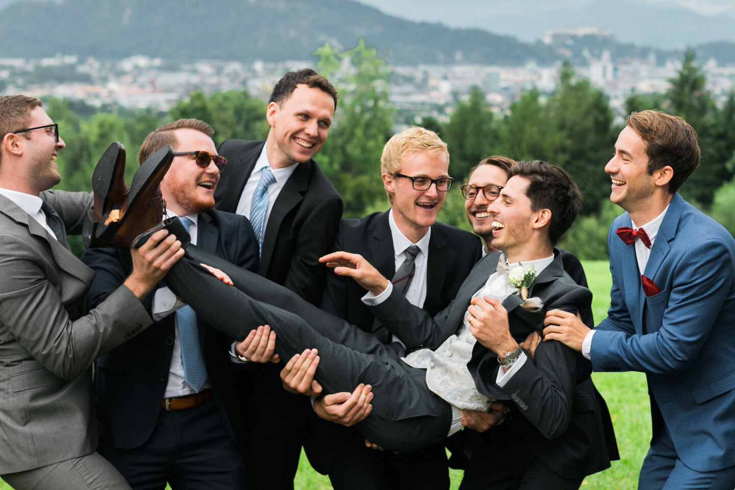 Wedding Photographer in Rome: Friends of the groom cheerfully throw him up and then catch him