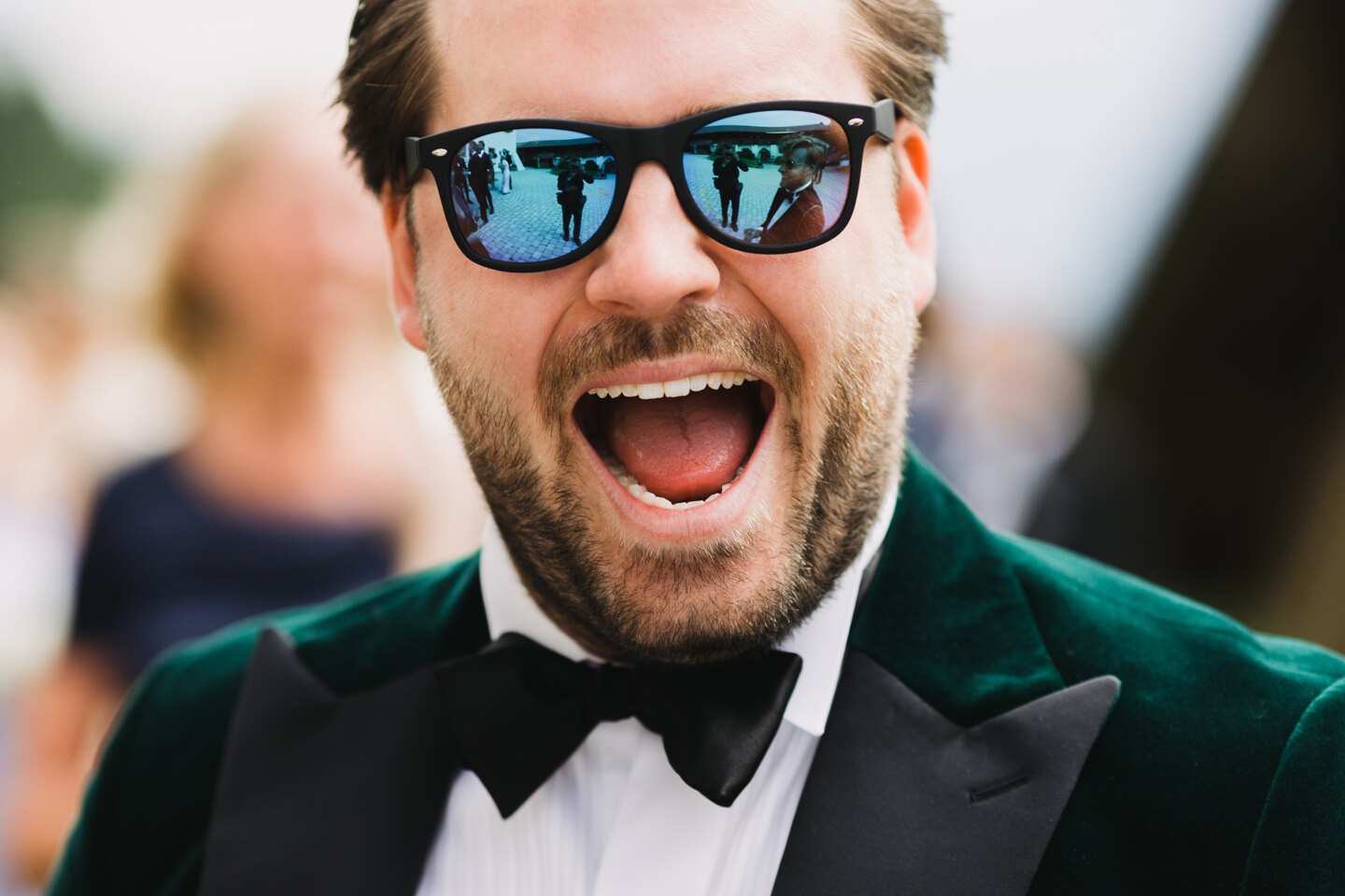 Wedding Photographer in Venice: Portrait of a groom in colored glasses, dressed in a green tuxedo with a bow tie on his neck and smiles broadly
