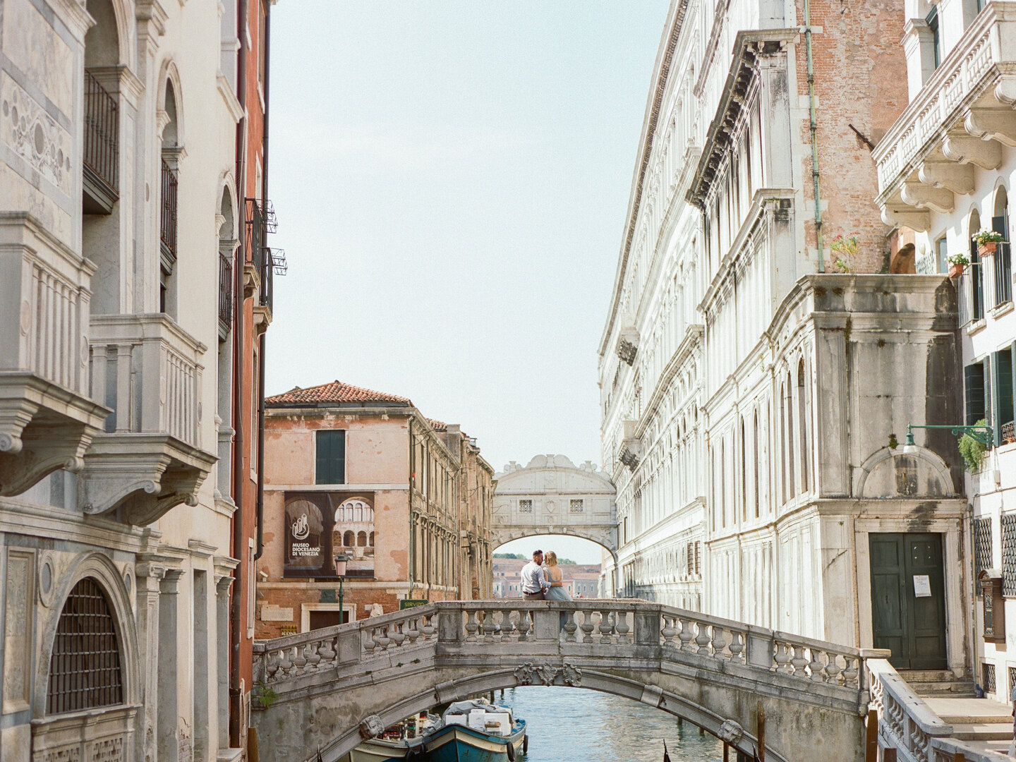 Wedding Photographer in Venice: A beautiful, young couple sits and gently hugs on one of the bridges of romantic and sunny Venice