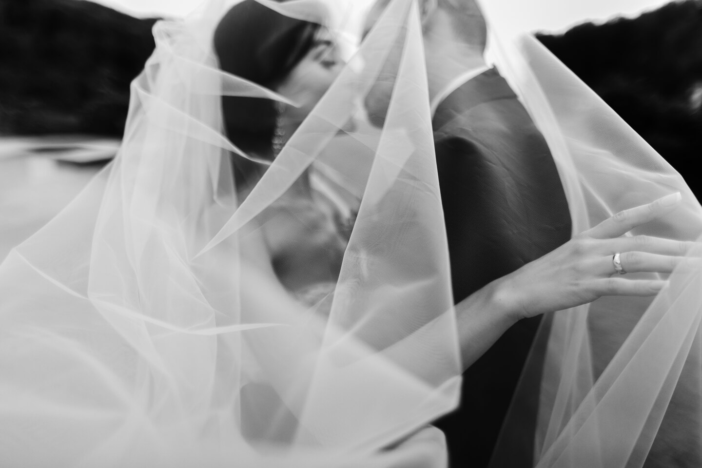 Wedding Photographer in Naples: Black and white frame where the bride and groom kiss and the wind wrapped them in a snow-white veil