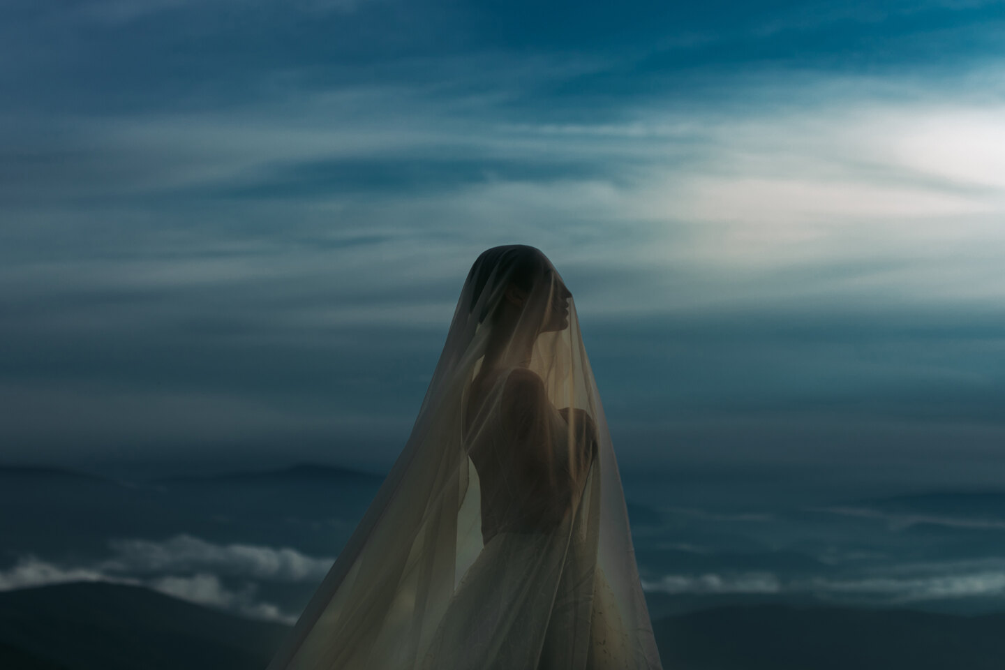Wedding Photographer in Naples: Portrait of a bride in a wedding dress with a veil that covers her face, against a blue sky