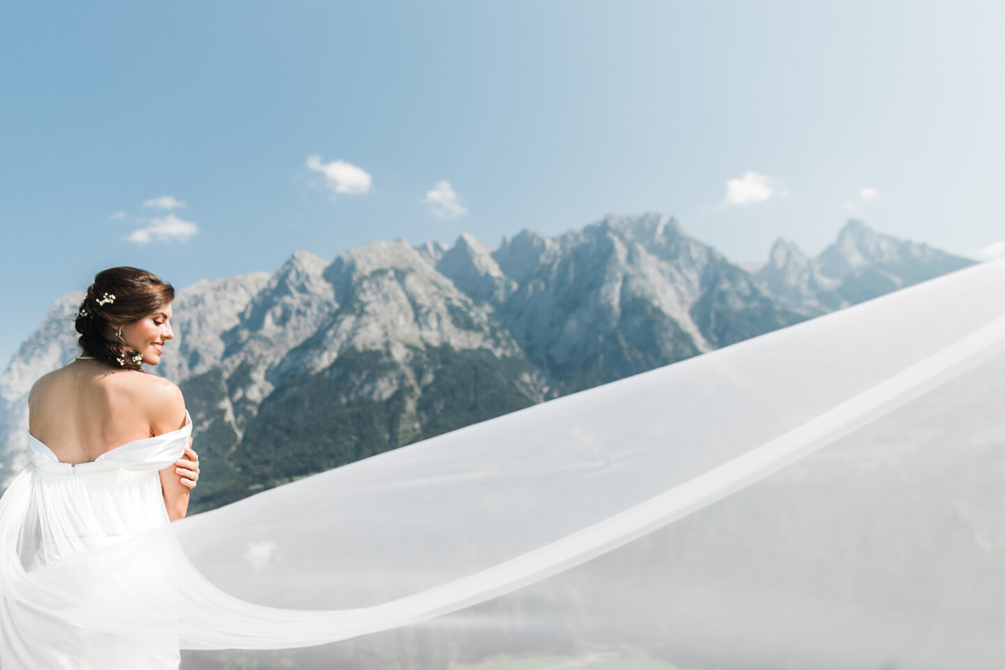 Wedding Photographer in Milan: The bride against the backdrop of luxurious mountains, the plume of her dress is widely dispelled by the wind, thereby emphasizing her fragile figure