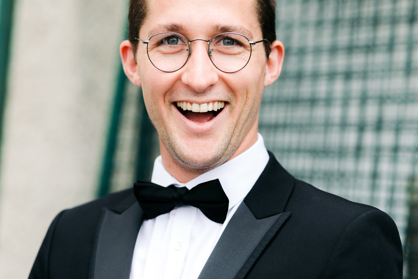 Wedding Photographer in Milan: Portrait of a groom in a black suit and glasses who smiles broadly into the frame