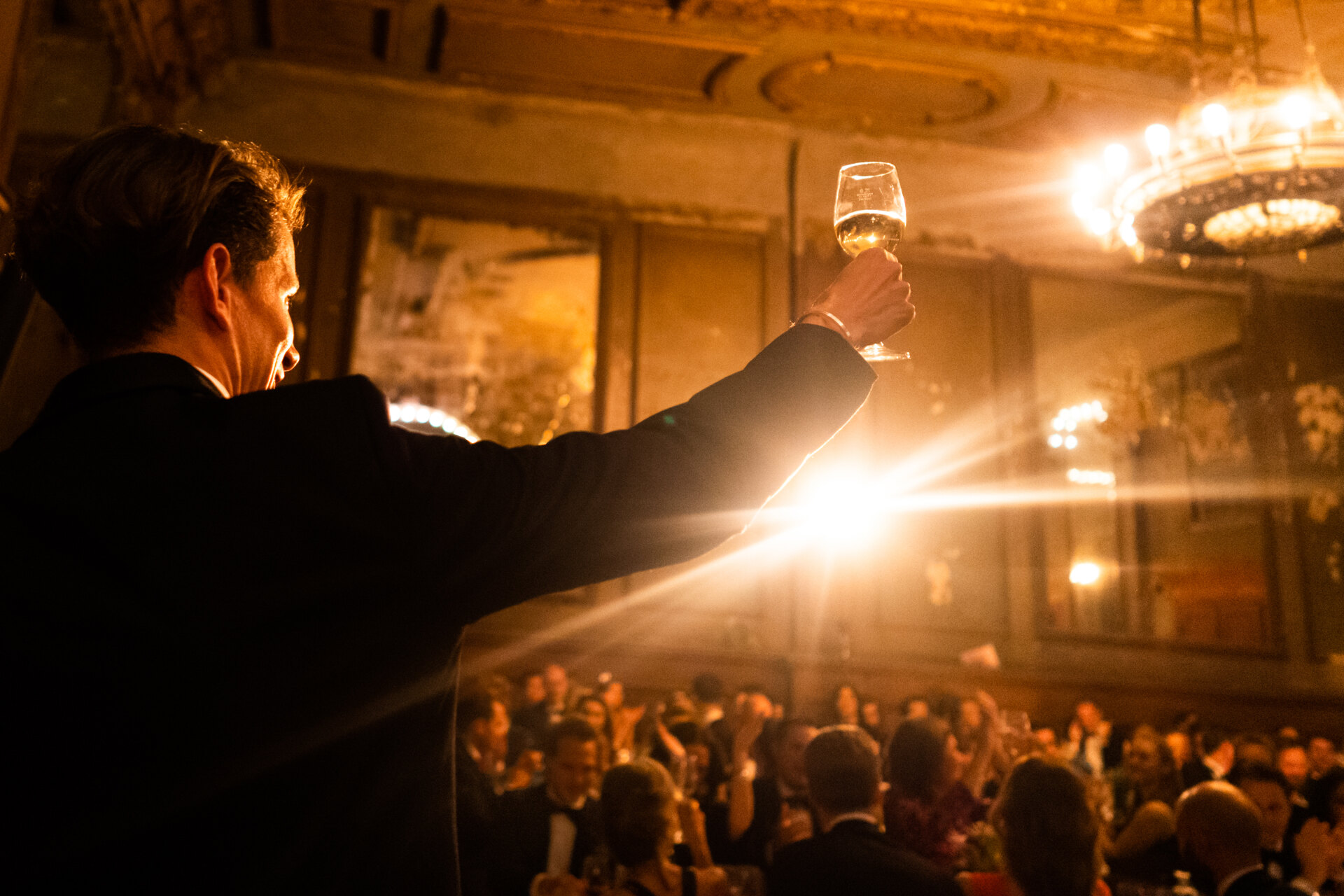Wedding photography portfolio in Italy: A man raises a glass of wine up in a large festive hall