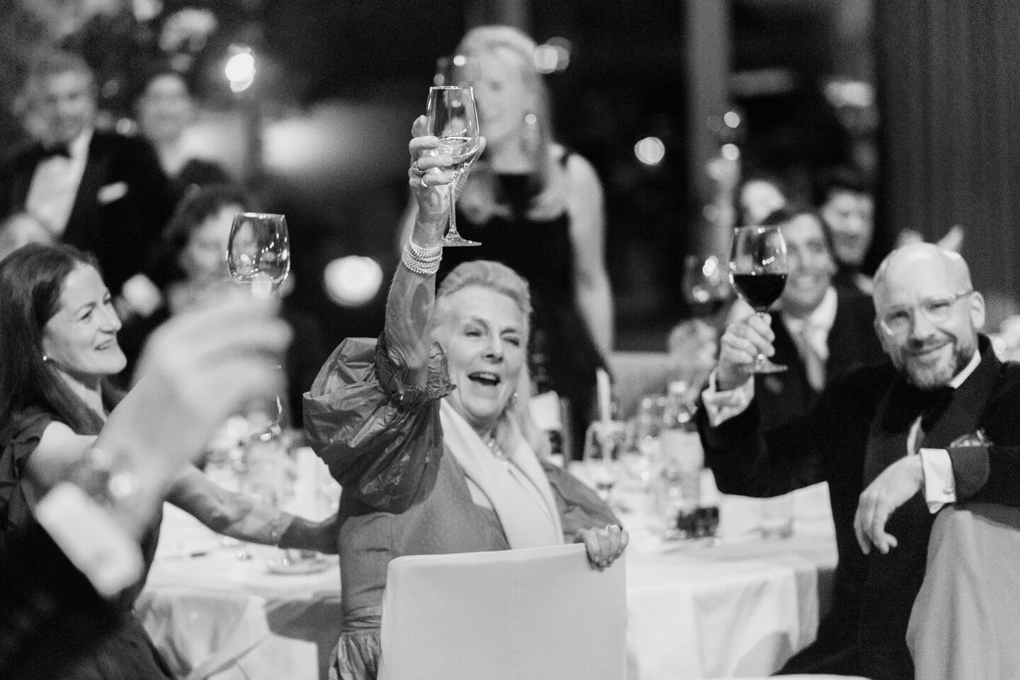 Services of Wedding Photographer in Italy: Cheerful, smiling guests raise their glasses up for the bride and groom