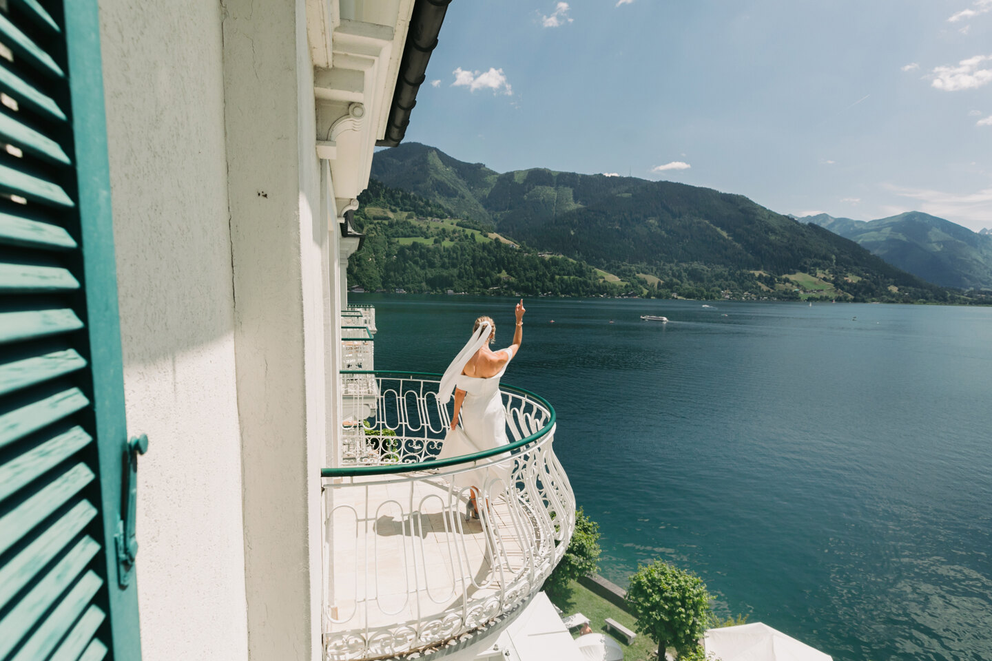 Services of Wedding Photographer in Italy: Bride in a white dress with a veil standing on the balcony of a luxury villa on the shores of Lake Como