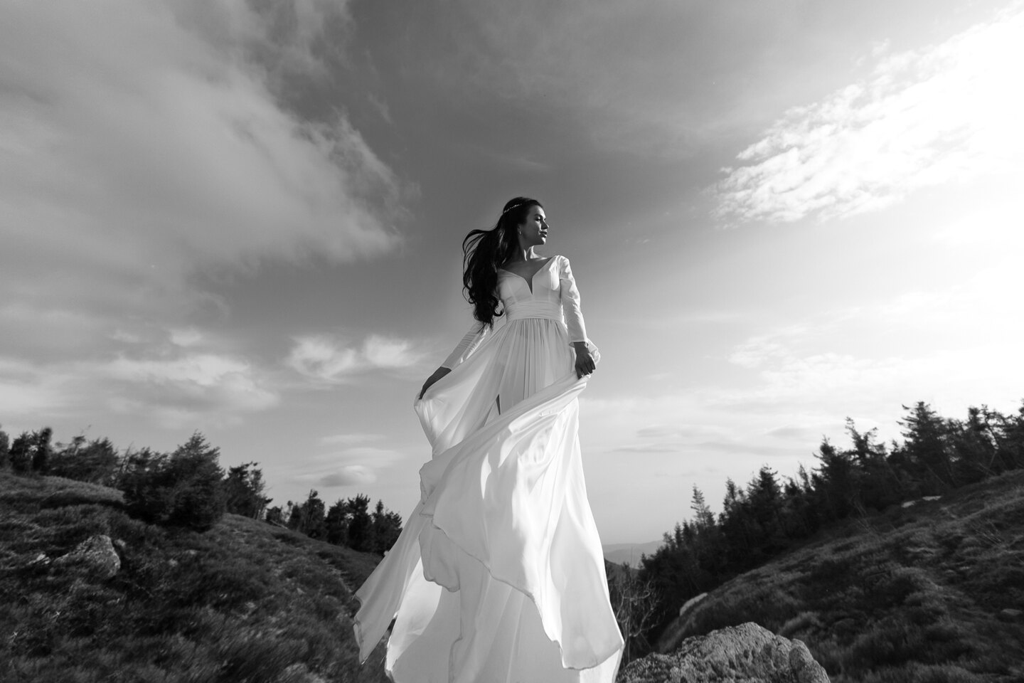 Services of Wedding Photographer in Italy: A fragile bride, stands on a hill among the trees, catches the wind with her dress and hair