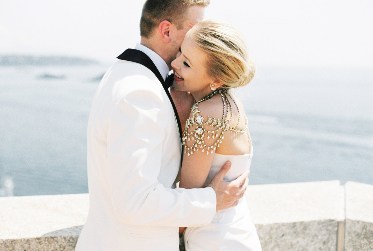 Services of Wedding Photographer in Italy: An exquisite and luxurious couple of newlyweds who are hugging on the background of the coast in Monaco. Groom in a white tuxedo hugs his smiling bride, who is dressed in a designer wedding dress decorated with s