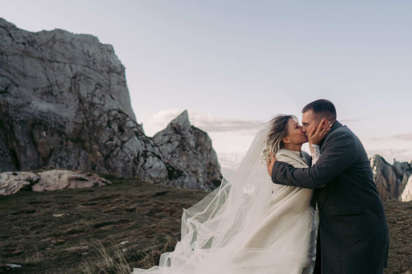 Couple photoshoot in Italy: Bride and groom kissing high in the mountains, despite the strong wind and cold