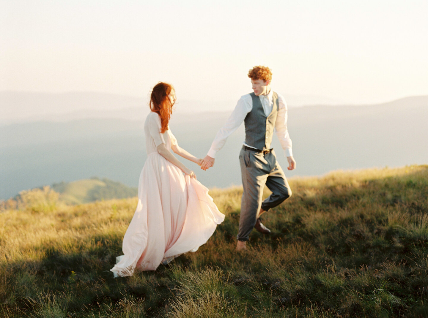 Couple photoshoot in Italy: An extraordinary couple of newlyweds with red hair, they walk along a sunny valley holding hands
