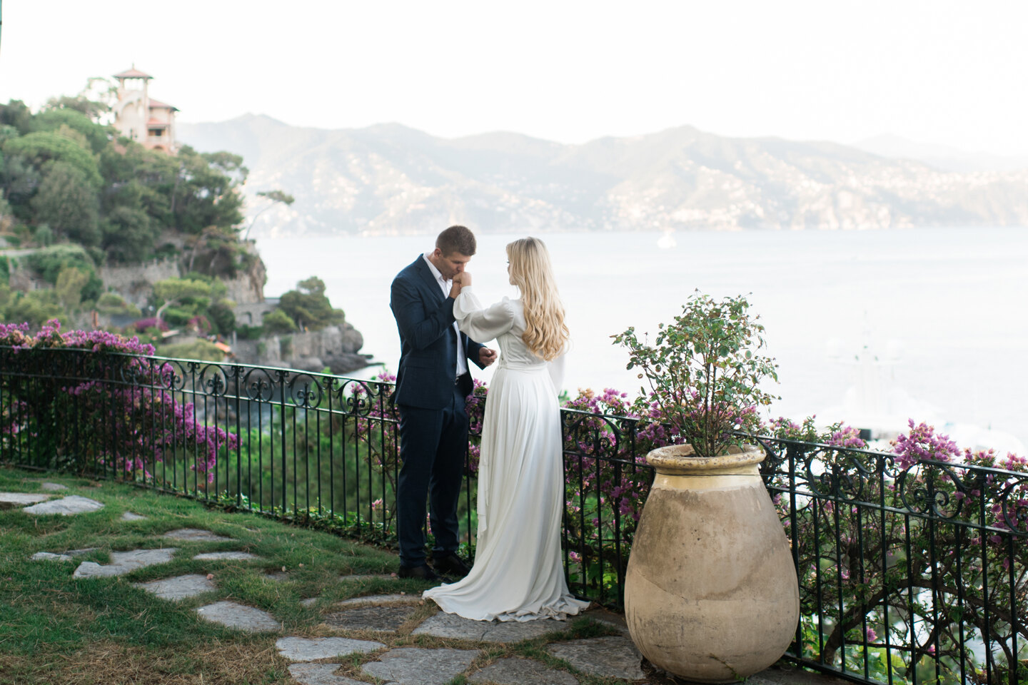 Couple photoshoot in Italy: Groom kisses the hand of his bride on the coast in Portofino
